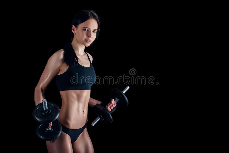 做健身锻炼的运动少妇反对黑背景 加大可爱的健身的女孩干涉与哑铃 免版税库存图片