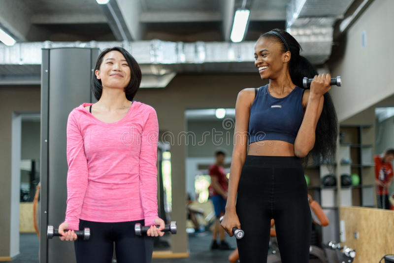 做健身锻炼的年轻黑人非裔美国人和亚裔性感的妇女夫妇一起与哑铃一起使用在 免版税图库摄影
