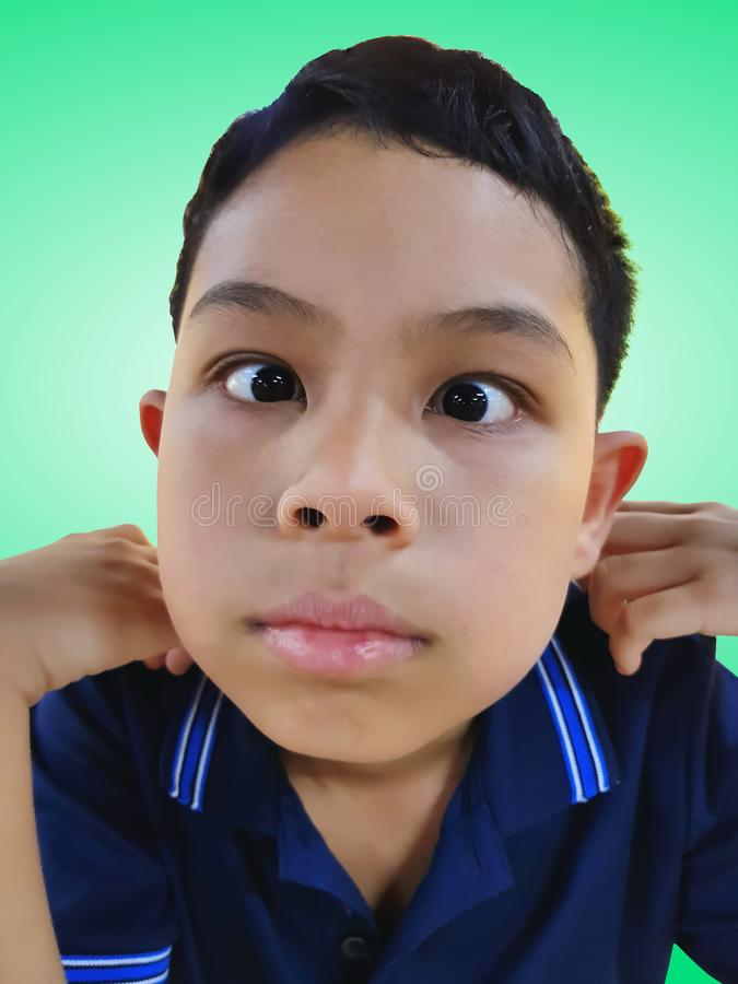 做傻的面孔的滑稽的男孩被隔绝在绿色背景 免版税图库摄影