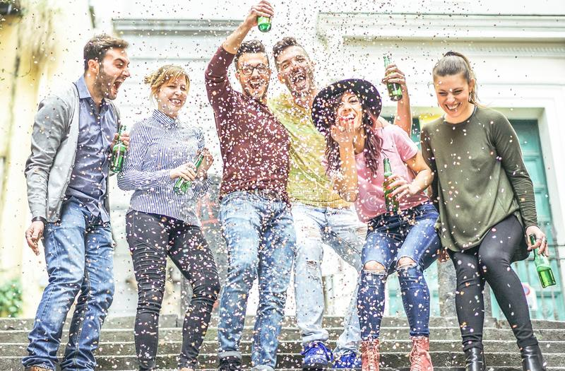 做党在市区-年轻人的小组愉快的朋友获得乐趣一起笑和喝室外的啤酒 图库摄影