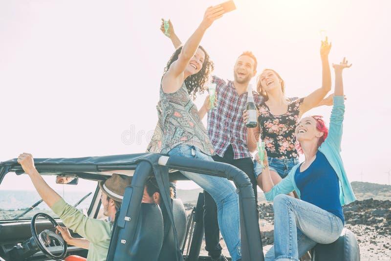 做党的小组愉快的朋友在有吉普车的年轻人乐趣饮用的香槟和照相selfie 免版税库存照片