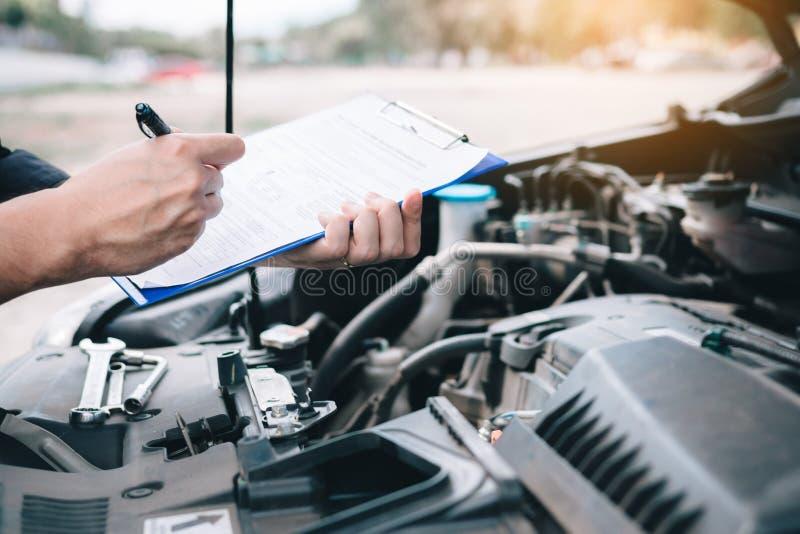 做关于纸剪贴板的亚裔汽车修理师一个清单和笔记报告 库存照片