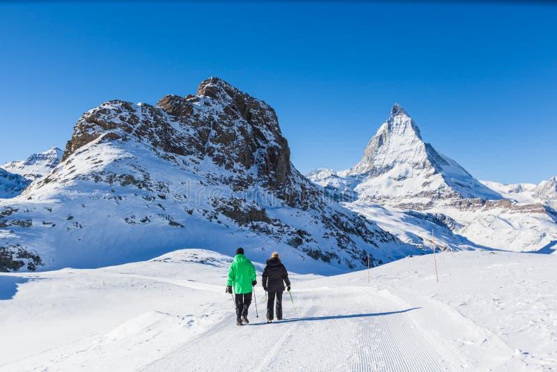 做冬天的资深夫妇远足在马塔角,策马特附近 图库摄影