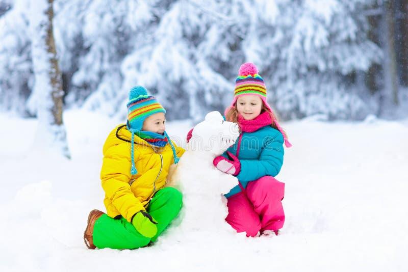做冬天雪人的孩子 在雪的儿童游戏 免版税库存照片