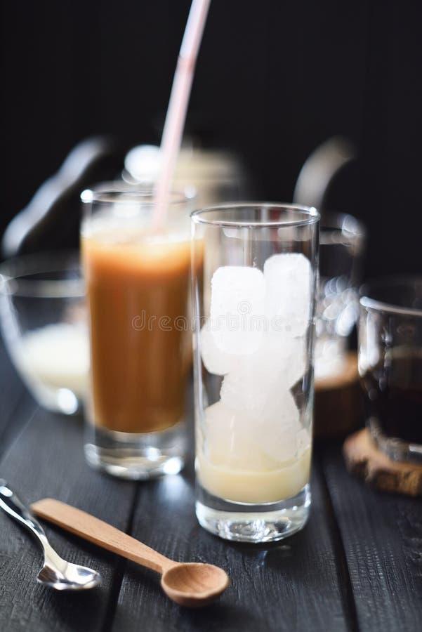 做冰冻咖啡 与冰块和浓缩牛奶的高玻璃准备好在黑背景的倾吐的咖啡 免版税图库摄影