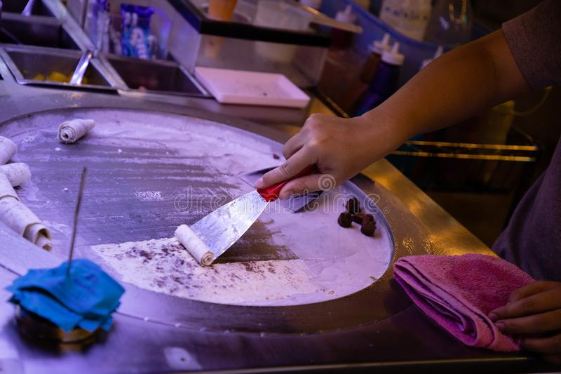 做冰淇淋的妇女手在圆的冷的板材 免版税库存照片