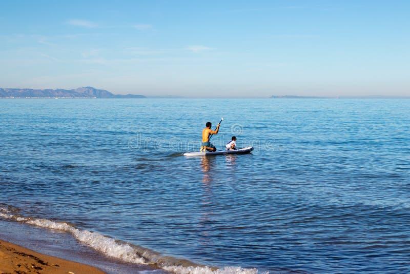 做冲浪在有一个小孩子的家庭的桨 库存照片