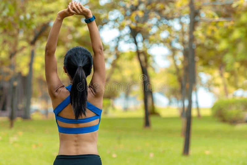 做准备健康的妇女舒展她的胳膊 在健身前的亚洲赛跑者妇女锻炼和在公园的跑步的会议 免版税库存照片