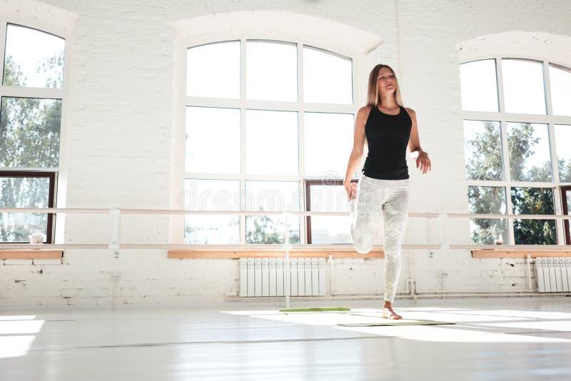 做准备和舒展在白色内部健身房的腿 做锻炼锻炼的健身妇女 库存图片