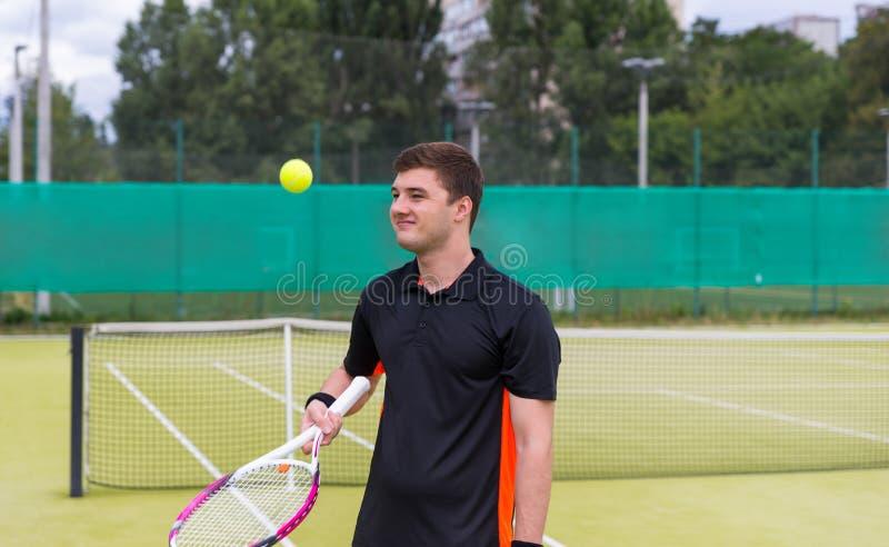 做准备在网球比赛前的英俊的男性网球员 免版税库存图片