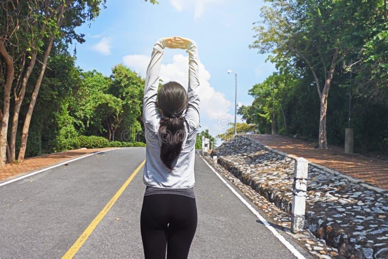 做准备在路的年轻健身妇女赛跑者舒展胳膊 免版税库存图片