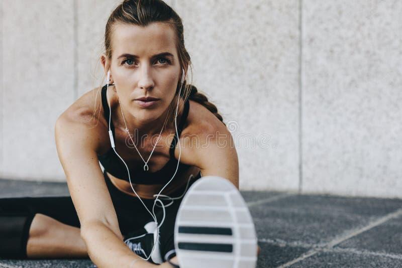 做准备女子的运动员做舒展行使户外 免版税库存图片