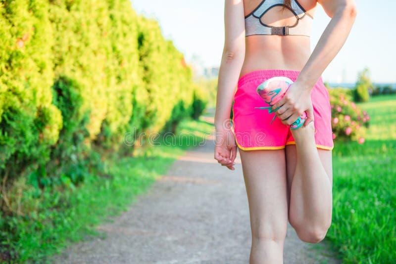做准备惯例的活跃妇女在公园在跑,舒展前腿干涉与站立唯一膝盖对胸口 库存图片