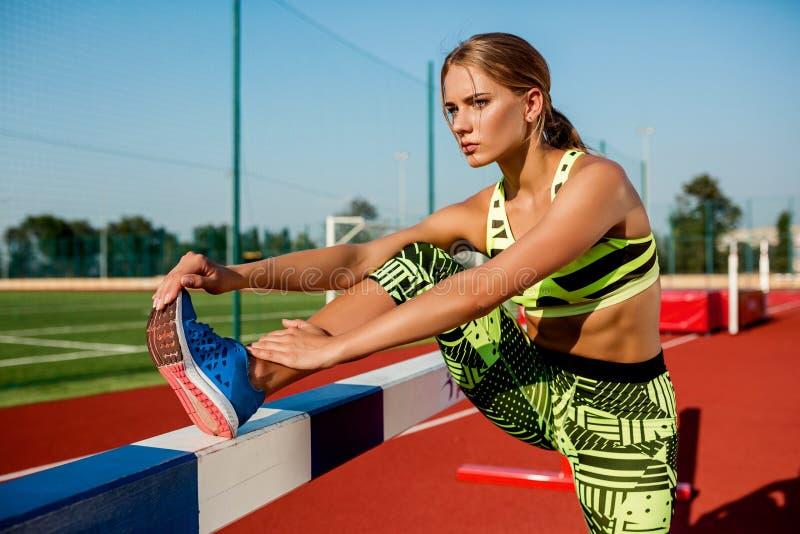 做准备的运动服的年轻,美丽的女孩运动员在体育场 图库摄影