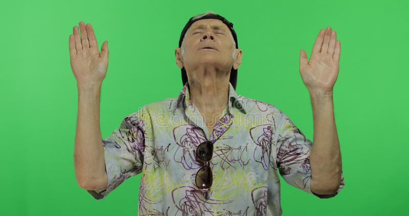 做凝思的五颜六色的衬衣的老人游人 英俊的老人 免版税库存图片