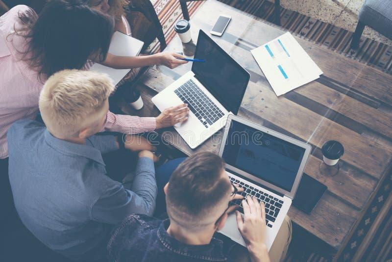 做出优秀商业决策的小组年轻工友队 创造性的现代人讨论公司工作的概念 免版税库存照片