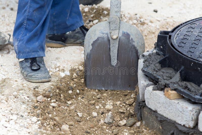 做出入孔设施的建筑工人 免版税库存图片