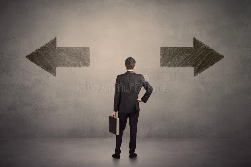 做出决定的商人,当站立在两gr前面时 库存照片