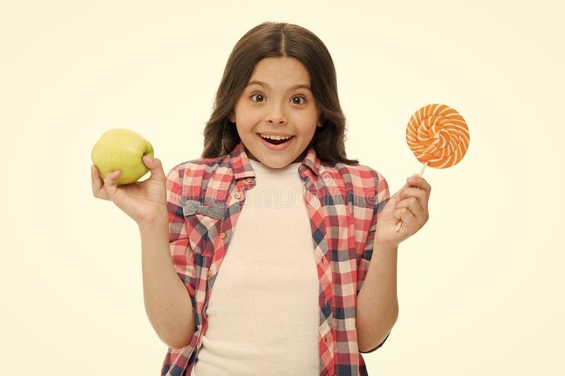 做出正确的选择 能加糖甜口味使我们愉快 女孩拿着甜棒棒糖和苹果 学校午餐选择 库存图片