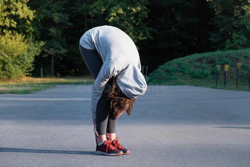 做初学者舒展的妇女瑜伽锻炼在公园 Fema 免版税库存图片