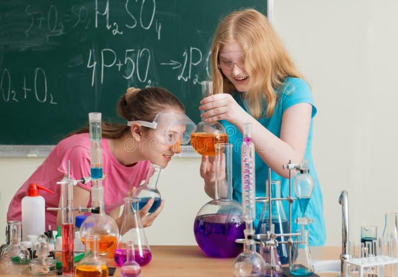 做化工实验的两个女孩 免版税库存照片