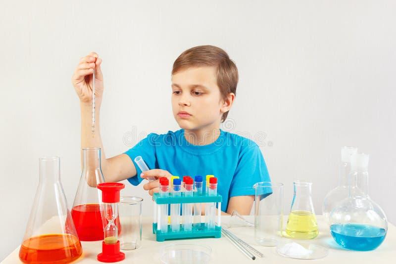 做化工实验的小聪明的男孩在实验室 免版税图库摄影