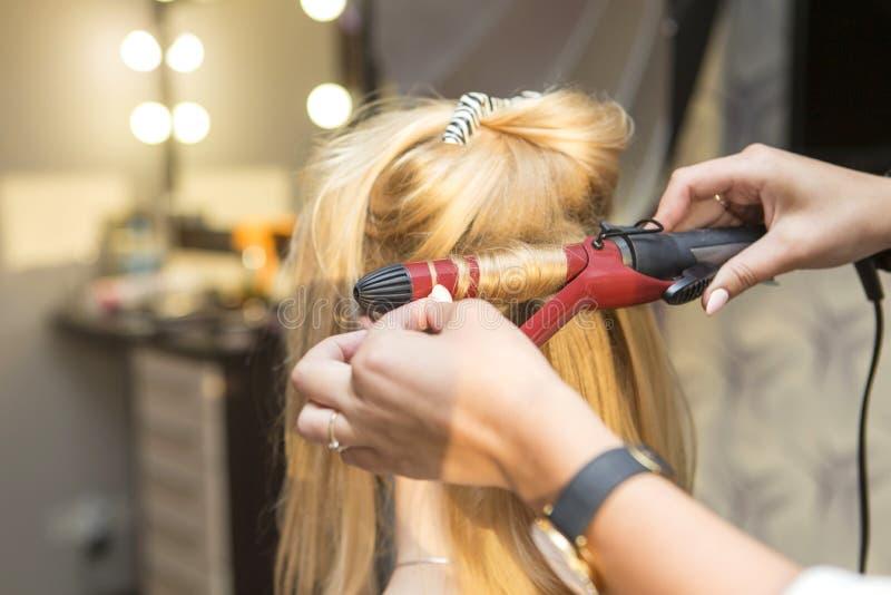 做卷曲发型的深色的红色头发美发师艺术家对b. 人们, 客户.