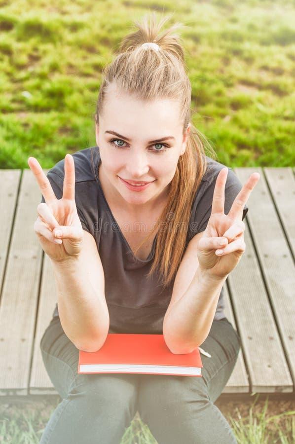 做双重和平或胜利姿态的愉快的微笑的女孩 免版税库存图片