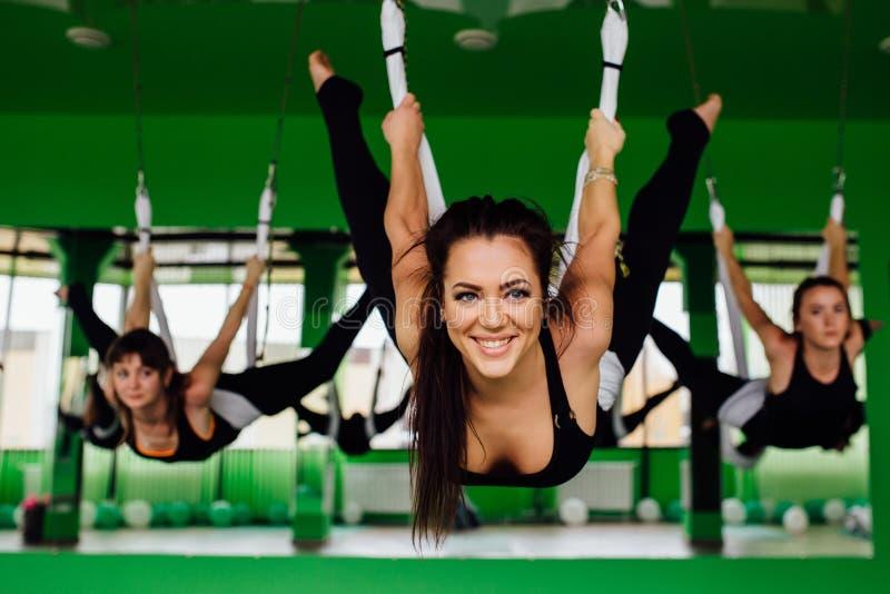 做反地心引力的瑜伽的少妇行使与一群人 航空飞行健身教练员锻炼 白色吊床 图库摄影