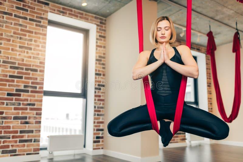 做反地心引力的瑜伽,在莲花坐的飞行的空中的妇女在红色吊床 库存图片