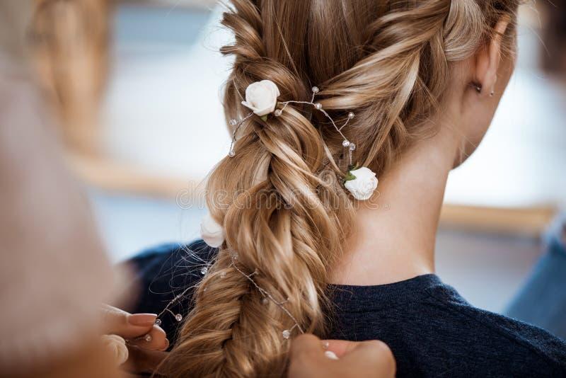 做发型的女性美发师对美容院的白肤金发的女孩 免版税库存图片