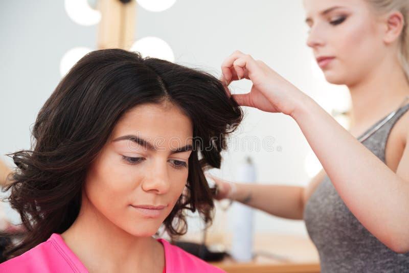 做发型的妇女美发师对年轻女性 图库摄影