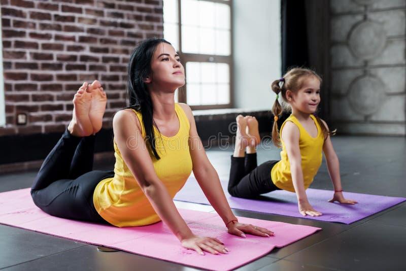 做另外年龄的两位女性的体操运动员舒展成拱形设法的锻炼接触有脚训练的头 免版税库存照片