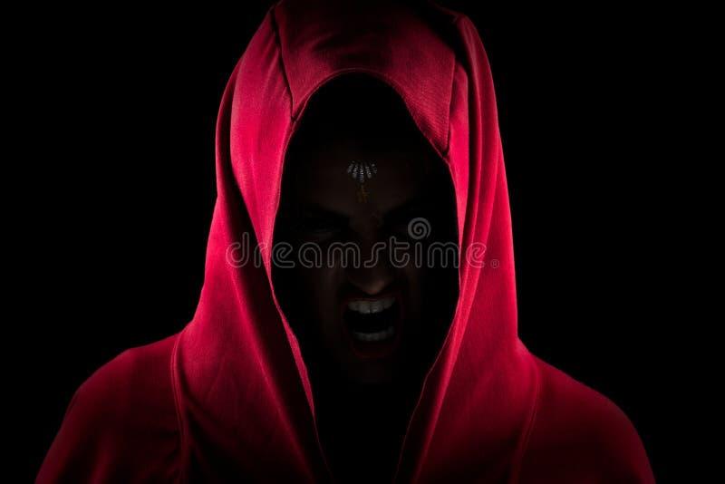 做可怕狼面孔的红色敞篷的女孩 免版税库存照片