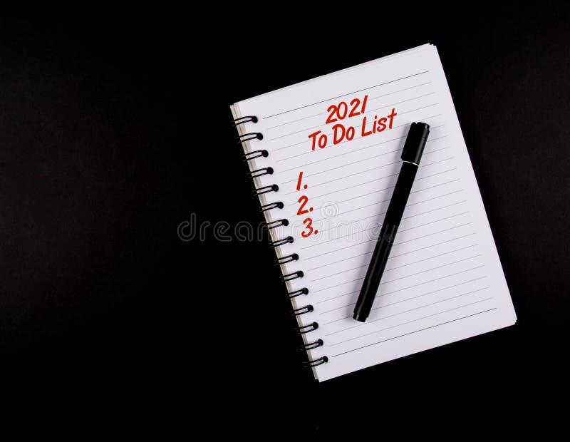 做名单年2021年,黑笔和笔记本,红色文本,隔绝在黑背景 免版税图库摄影