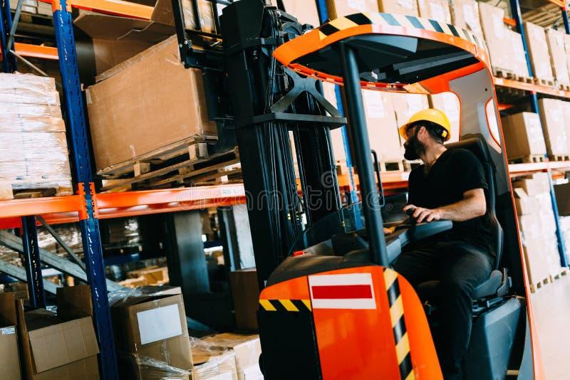 做后勤学的仓库工作者与铲车装载者一起使用 免版税库存图片