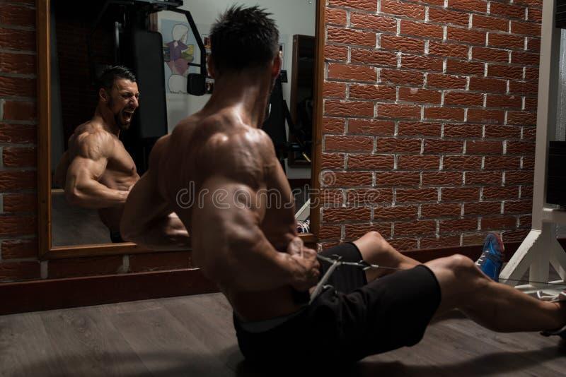 做后面的年轻爱好健美者重量级的锻炼 免版税库存照片