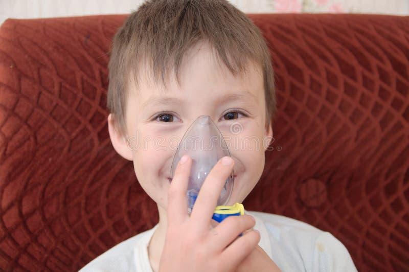 做吸入、呼吸做法由肺炎或咳嗽的雾化器面具的病的男孩 免版税库存图片