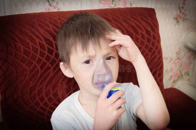 做吸入、呼吸孩子的雾化器面具的病的男孩做法由肺炎或咳嗽 图库摄影