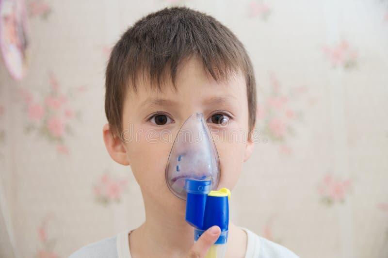 做吸入、呼吸孩子的雾化器面具的病的男孩做法由肺炎或咳嗽 库存照片