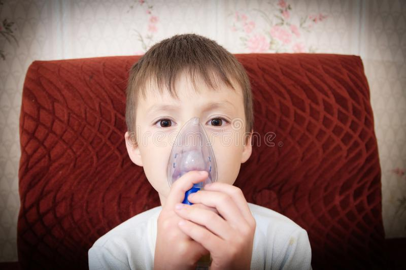 做吸入、呼吸孩子的,吸入器的雾化器面具的病的男孩做法由肺炎或咳嗽 库存图片