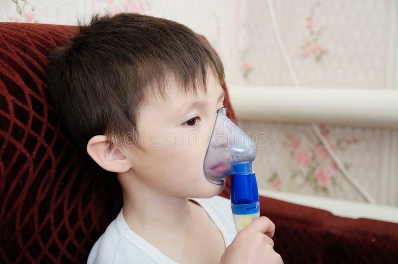 做吸入、呼吸孩子的,吸入器的雾化器面具的病的男孩做法由肺炎或咳嗽 库存照片