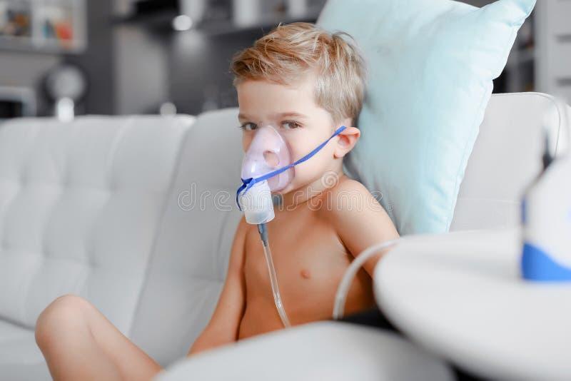 做吸入、呼吸孩子的,吸入器,压缩机的雾化器面具的病的男孩做法由肺炎或咳嗽 图库摄影