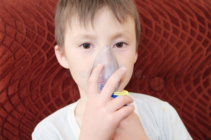 做吸入,由肺炎的呼吸做法的雾化器面具的病的男孩 库存图片