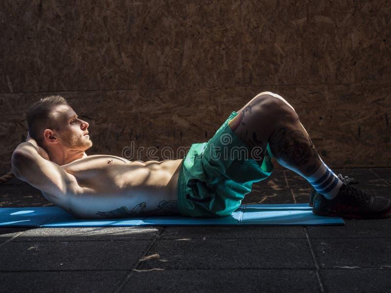 做吸收的健身房的年轻人锻炼 免版税图库摄影