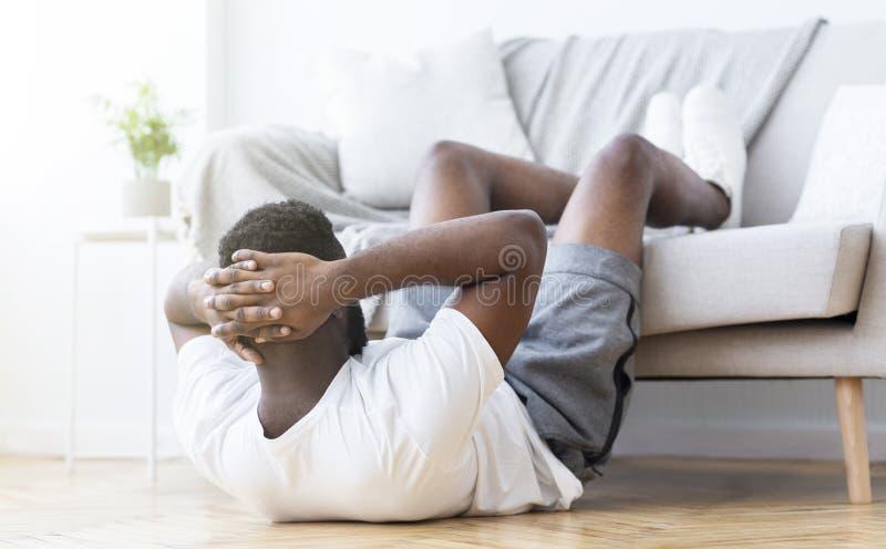 做吸收训练和咬嚼的黑人在客厅 免版税库存照片