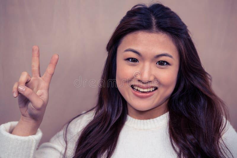 做和平标志的微笑的亚裔妇女 免版税库存照片