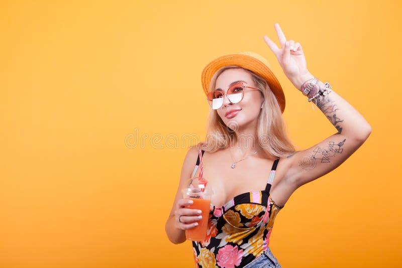做和平标志的迷人的少妇,当食用新鲜的橙汁时 免版税图库摄影
