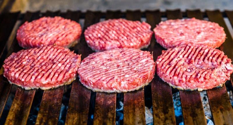 做和烤汉堡包牛肉小馅饼在煤炭烤 免版税库存照片