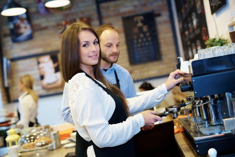 做咖啡的可爱的女服务员 免版税库存图片